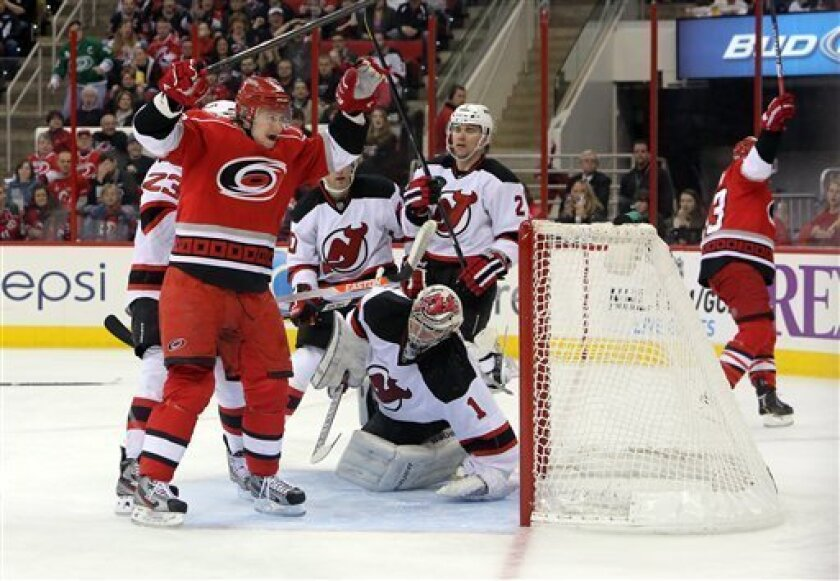 Carolina Hurricanes' Jussi Jokinen, left, of Finland, celebrates a goal by teammate Jeff Skinner, right, against New Jersey Devils' goalie Johan Hedberg (1), of Sweden, and defender Marek Zidlicky (2), of the Czech Republic, during the second period of an NHL hockey game in Raleigh, N.C., Saturday,