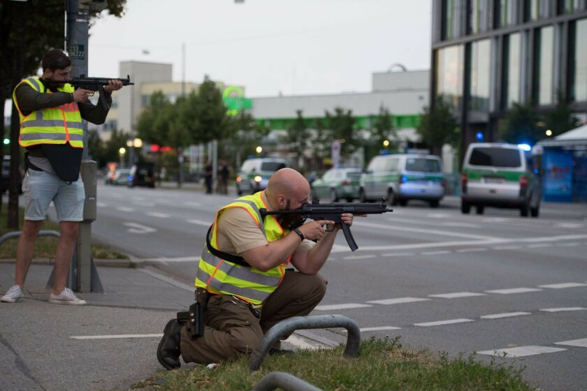 Police officers point their weapons outside the Olympia mall in Munich, southern Germany, Friday, July 22, 2016 after several people have been killed in a shooting. (AP Photo/Sebastian Widmann)