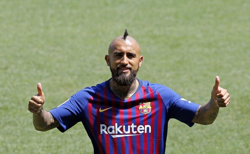 El mediocampista chileno Arturo Vidal saluda durante su presentación oficial como nuevo miembro del club Barcelona el lunes 6 de agosto de 2018, en el Camp Nou de Barcelona, España.