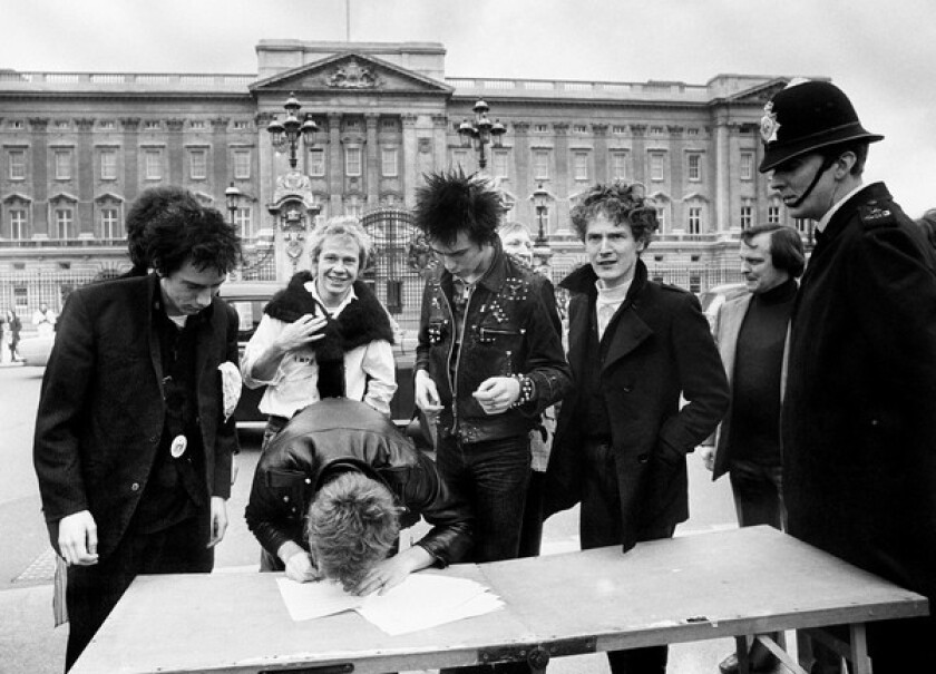 The Sex Pistols sign a new recording contract with A&M Records outside Buckingham Palace in 1977. From left are Johnny Rotten, Paul Cook (in back), Steve Jones, Sid Vicious and the band's manager, Malcolm McLaren. See full story