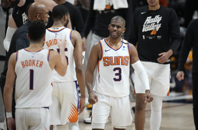 Phoenix Suns guard Chris Paul congratulates teammates during a timeout in the second half of Game 4 of an NBA second-round playoff series against the Denver Nuggets, Sunday, June 13, 2021, in Denver. (AP Photo/David Zalubowski)