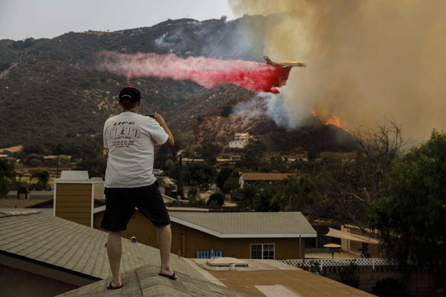 Jeff Qualls stands on his roof to watch an air tanker drop fire retardant on flames from the Holy fire as it make its way down the hillside in Lake Elsinore, Calif.