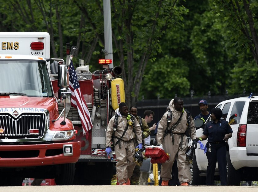 Men in what appears to be a hazardous materials suits by the Northwest gate of the White House in Washington, Monday, May 30, 2016.  Secret Service spokesman Robert Hoback says someone at about 12:15 p.m. threw a metal object over the north fence along Pennsylvania Avenue and was arrested without i