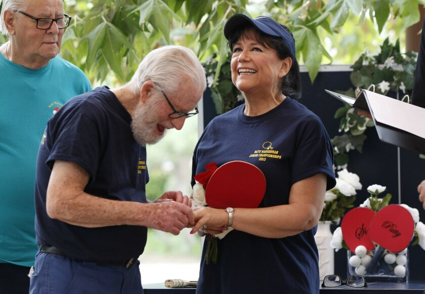 "Si Wasserman, 94, places the wedding ring on the finger of table tennis partner Patty Martinez, 64, during their wedding ceremony at the El Corazon Senior Center in Oceanside on Wednesday. At left is Jack Wetherbie, one of Wasserman's two ""best man"" attendants."