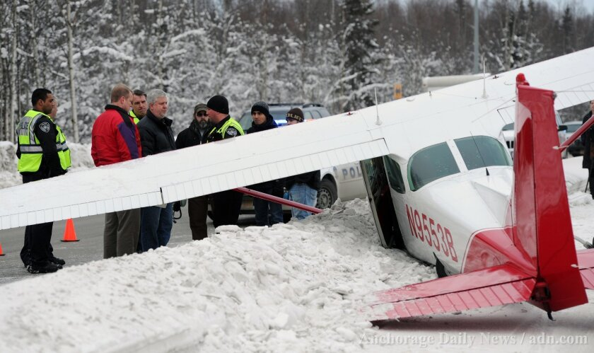 A plane rests in the northbound lane of Boniface Parkway following an emergency landing near Perry Drive south of DeBarr Road Tuesday, Jan. 7, 2014 in Anchorage, Alaska. Anchorage police say a plane with three people on board made an apparent emergency landing on the median of a major street. (AP Photo/The Anchorage Daily News, Erik Hill) LOCAL TV OUT (KTUU-TV, KTVA-TV) LOCAL PRINT OUT (THE ANCHORAGE PRESS, THE ALASKA DISPATCH)