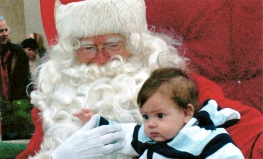Santa chats with a young boy at a previous La Jolla holiday festival. Photo: Courtesy