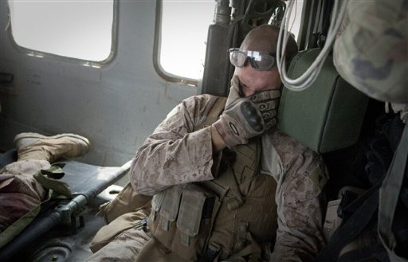 "United States Marine Joshua Barron reacts onboard a medevac helicopter from the US Army's Task Force Lift ""Dust Off"", Charlie Company 1-214 Aviation Regiment, after he was wounded in an IED strike near Sangin, in the Helmand Province of southern Afghanistan, Saturday, June 4, 2011.(AP Photo/Anja Niedringhaus)"