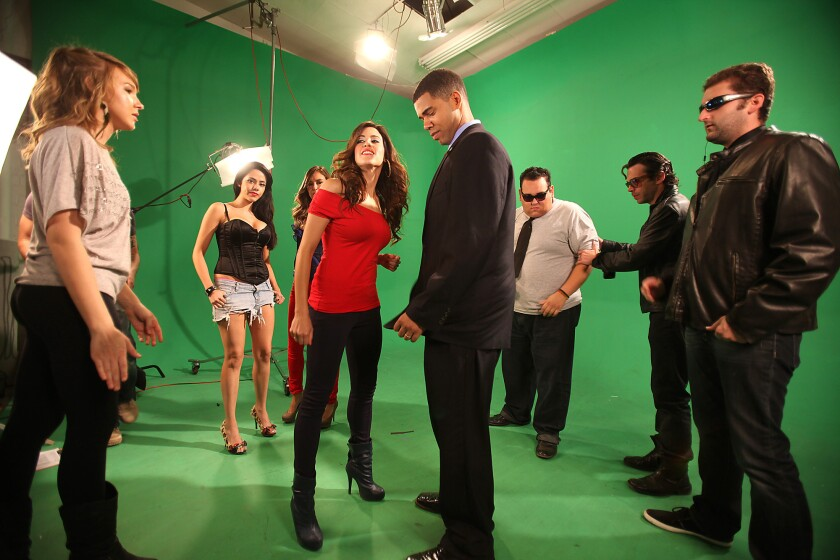 Actors and production staff rehearse for a music video shoot on a green screen set at Maker Studios in 2011.