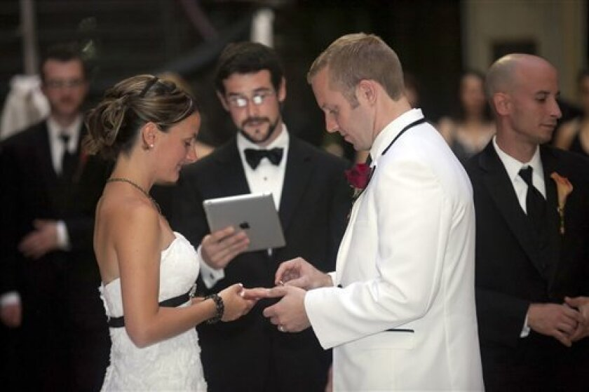 This Sept. 10, 2011 photo courtesy of Fisher Creative Image shows groom Steve Poland, right, and bride Caryn Hallock during their wedding ceremony in Buffalo, N.Y. Robert Palgutt, center, a friend of the bride and groom, got ordained online in order to perform their ceremony and read the nuptials from an iPad. (AP Photo/Fisher Creative Image)