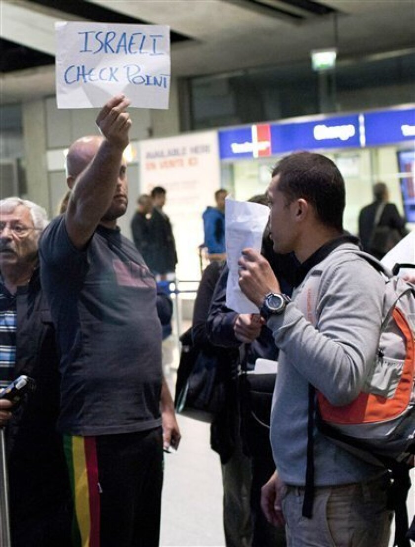 Pro-Palestinians activists protest at Charles de Gaulle airport, north of Paris, as they are blocked by police at the airport, Friday, July, 8, 2011. Israel increased security at the Ben-Gurion International Airport ahead of the activists' arrival and asked foreign airlines to prevent blacklisted travelers from boarding Israel-bound flights, as hundreds said they would travel to Israel to protest Israeli policies toward the Palestinians.(AP Photo/Thibault Camus)