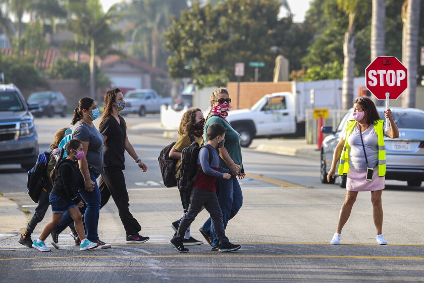 A crossing guard on Wednesday helps students return to in-person instruction at James H. Cox Elementary School.