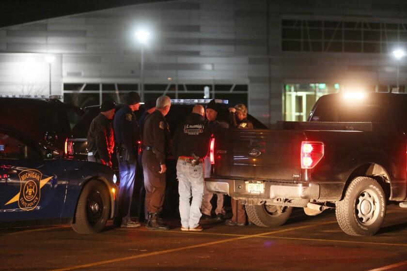Varios policías intercambian informaci´no en la madrugada del domingo 21 de febrero del 2016 frente al Colegio Comunitario de Kalamazoo Valley después de buscar a un individuo que dejó seis muertos en Kalamazoo, Michigan. (Mark Bugnaski/Kalamazoo Gazette via AP) MANDATORY CREDIT