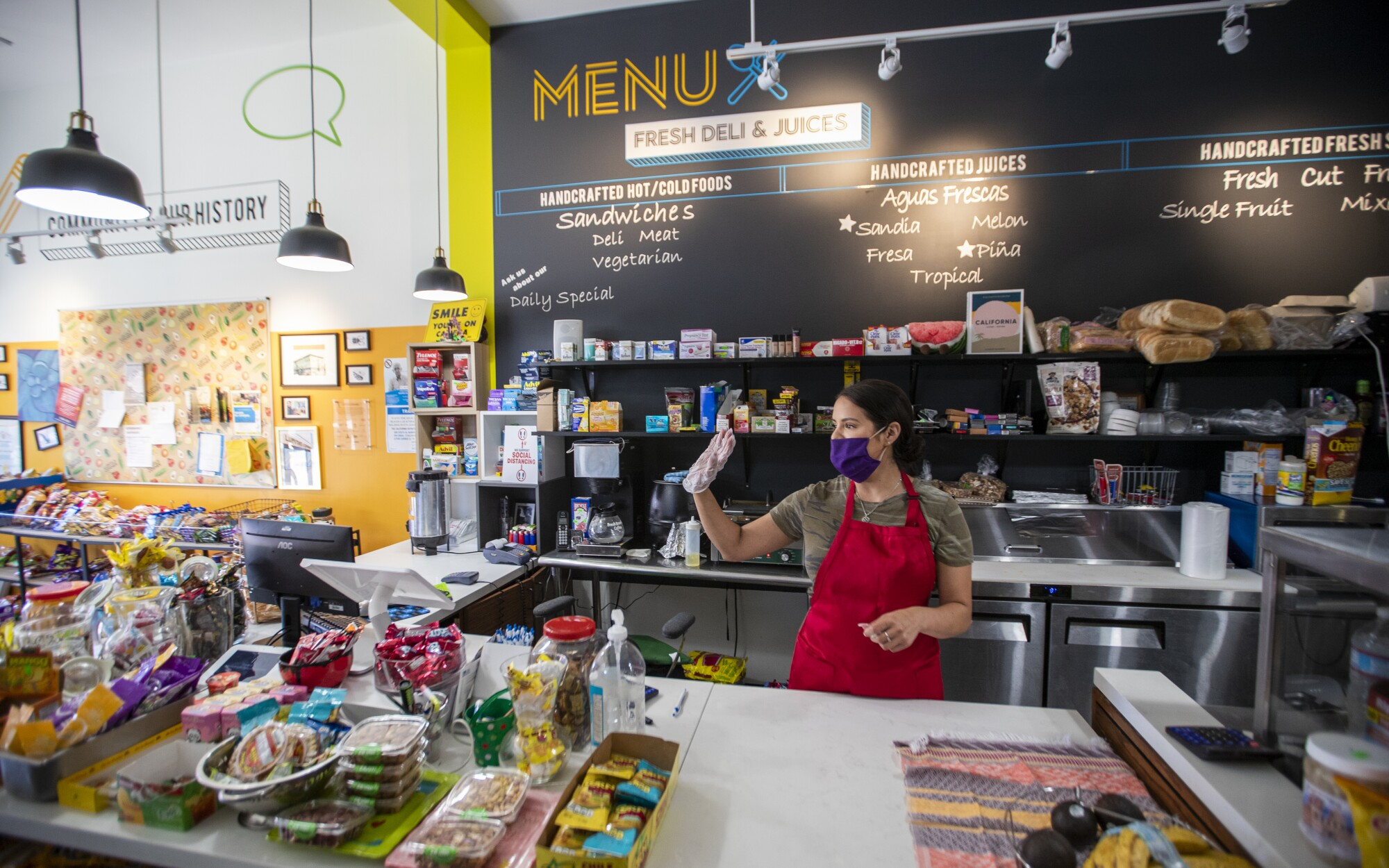 Luz Arango waves at a regular patron at Lupita's Corner Market and Deli in L.A.'s Westlake District