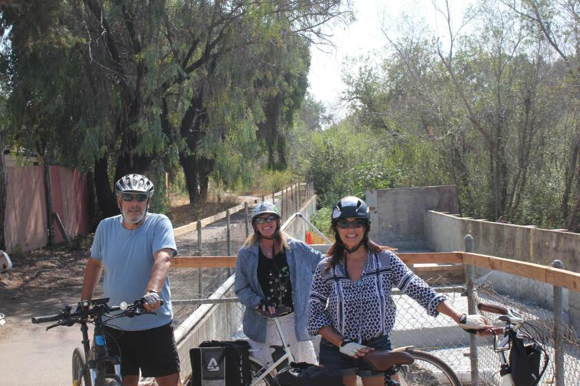 Nicole Burgess (center) is PB's rep on the City's Bicycle Advisory Board. She takes a break with friends Steven and Kristen Victor during a recent ride on the Rose Creek pathway.