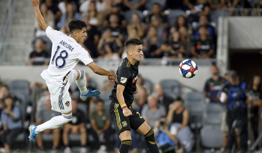 Galaxy midfielder Uriel Antuna, left, and LAFC midfielder Eduard Atuesta battle for the ball during the first half on Aug. 25.
