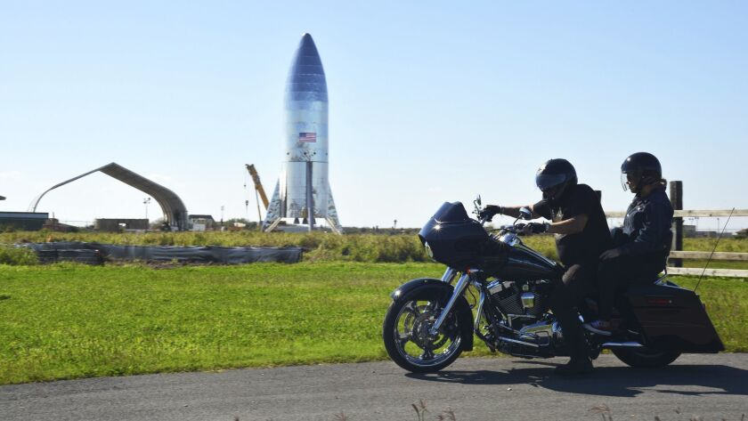 A motorcyclist rides near the SpaceX prototype Starship hopper vehicle at Boca Chica Beach, Texas, on Jan. 12.