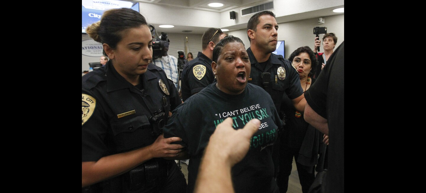 Civil rights activist Tasha Williamson, who is handcuffed, is escorted out the National City council chambers by police after her outburst while speaking about the death of Earl McNeil.
