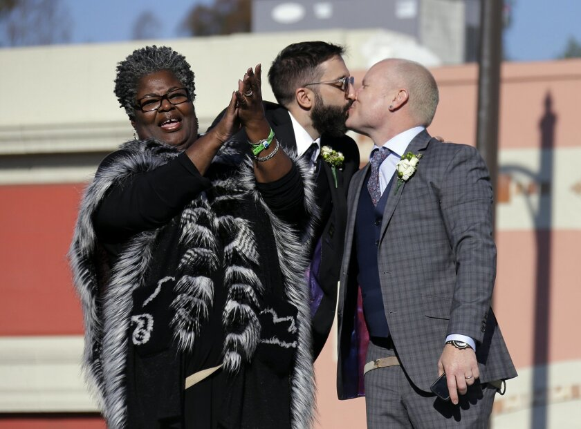 Aubrey Loots, right, and Danny Leclair, the first gay couple to be married aboard a float in the Tournament of Roses, kiss after being wed by the Rev. Alfreda Lanoix of the Unity Fellowship Church of Christ, left, aboard the AIDS Healthcare Foundation float in the 125th Rose Parade in Pasadena, Cal