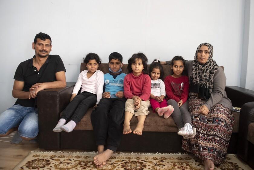Abdul Salam Al Khawien (izq), su esposa Kariman (der) y sus cinco hijos posan para una foto en la casa donde viven en Salónica, Grecia, el 1ro de mayo del 2021. Padre e hijos escaparon de Siria después de un bombardeo, convencidos de que la madre había muerto. Tres años después, sin embargo, se enteraron de que había sobrevivido y la familia pudo reunirse en Grecia. (AP Photo/Giannis Papanikos)
