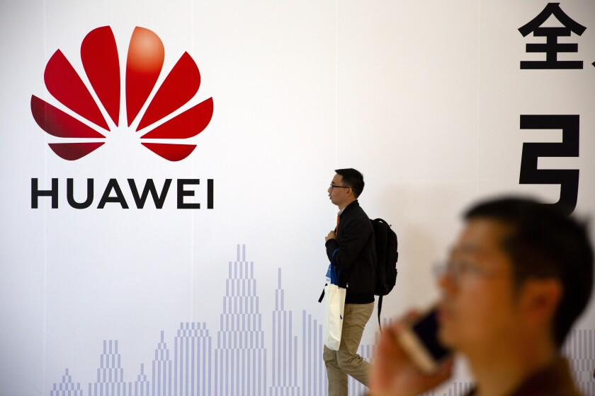 Men walk in front of a Huawei sign at a tech expo in Beijing in 2019