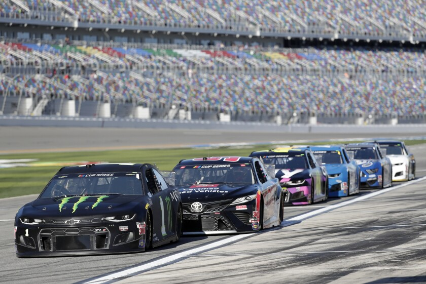 Kurt Busch, left, leads a pack of cars on pit road as they wait to go out on the track during a NASCAR auto race practice at Daytona International Speedway, Saturday, Feb. 8, 2020, in Daytona Beach, Fla. (AP Photo/John Raoux)