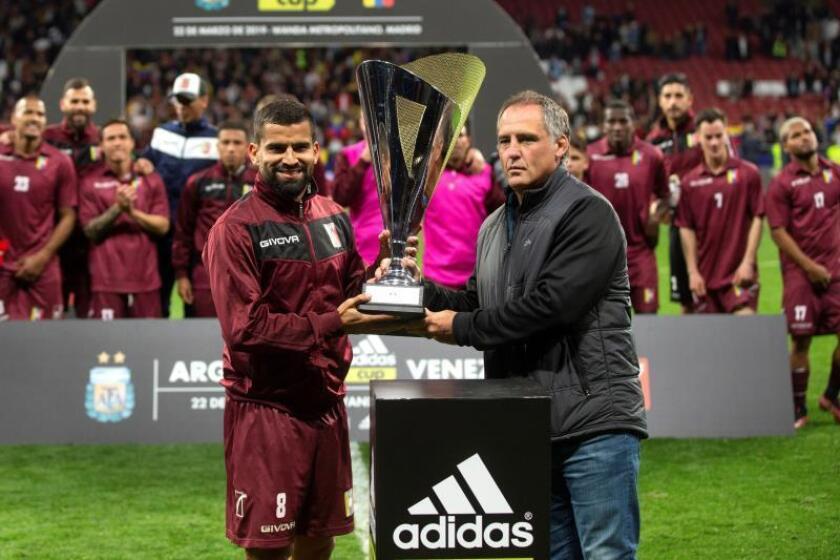 El centrocampista de la selección de Venezuela Tomás Eduardo Rincón (i) recibe el trofeo tras vencer a Argentina por 1-3 en el encuentro amistoso que disputaron esta noche en el estadio Wanda Metropolitano, en Madrid. EFE/Rodrigo Jiménez