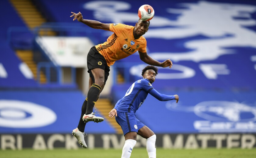 Chelsea's Willian, right, watches Wolverhampton Wanderers' Willy Boly leaping for a header during the English Premier League soccer match between Chelsea and Wolverhampton Wanderers at Stamford Bridge, in London, Sunday July 26, 2020. (Daniel Leal-Olivas/Pool via AP)