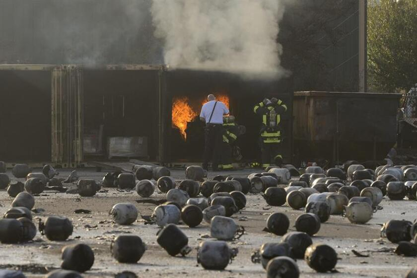 Bombonas de butano permanecen esparcidas por el suelo mientras los bomberos continúan intentando apagar pequeños incendios en los alrededores de la compaía de gas Blue Rhino en Tavares, Florida (Estados Unidos), el martes 30 de julio de 2013. EFE/Archivo