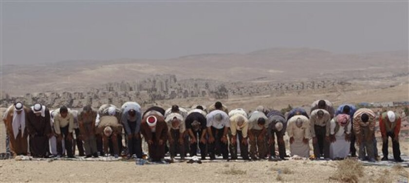 Palestinians pray during Friday prayers as the Jewish settlement of Maale Adumim is seen in the background, on a hilltop next to the West Bank Jewish settlement of Qedar, Friday, June 5, 2009. Israel will not heed US President Barack Obama's powerful appeal to halt all settlement activity on lands