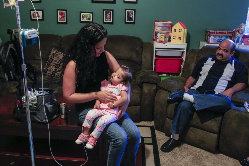 Sadie Christina Higuera, 1, (will be 2 on May4th) spends time at home with her parents Damaris (left) and Brian (right) on Friday evening in Ramona, California. Sadie has a rare genetic disorder and a medical marijuana based substance  has almost stopped the 300/day seizures she was having.