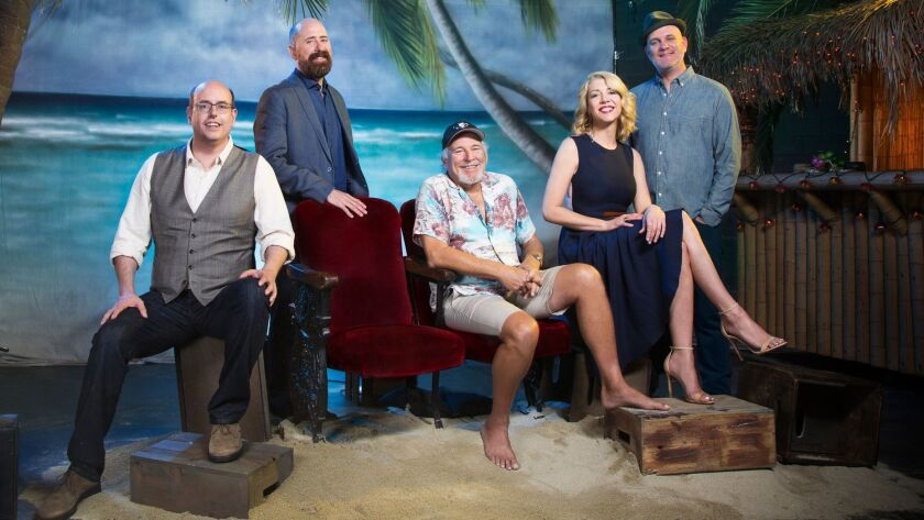 "Jimmy Buffett (seated, center) with the ""Escape to Margaritaville"" creative team (from left): director Christopher Ashley, writer Greg Garcia, choreographer Kelly Devine and writer Mike O'Malley."