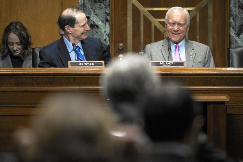Sen. Ron Wyden (D-Ore.), left, the ranking Democrat on the Senate Finance Committee, and Sen. Orrin G. Hatch (R-Utah), the Senate panel's chairman, converse during the panel's Thursday hearing.