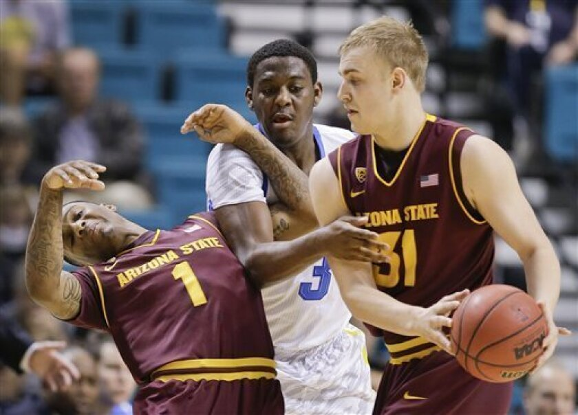Arizona State's Jahii Carson (1) gets tangled up with UCLA's Jordan Adams (3) as Jonathan Gilling (31) tries to hand the ball off during the first half during a Pac-12 Conference tournament NCAA college basketball game, Thursday, March 14, 2013, in Las Vegas. (AP Photo/Julie Jacobson)