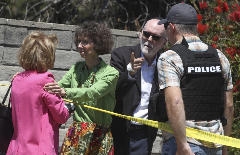 Members of Chabad of Poway talk to a police officer April 27 after a gunman killed one woman in the synagogue and wounded several others.
