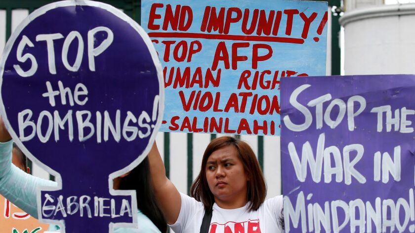 Demonstrators in Manila on July 7 protest Philippine President Rodrigo Duterte's declaration of mart