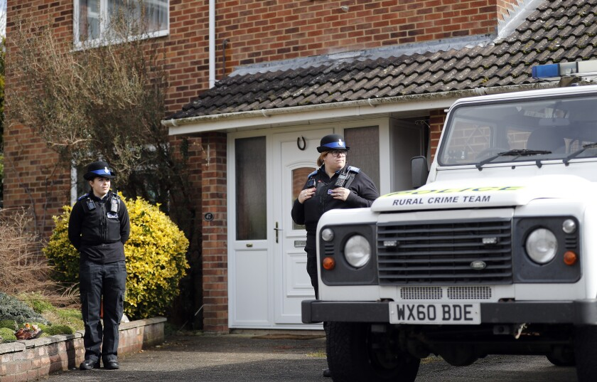 """FIle - In this Tuesday, March 6, 2018 file photo, police officers stand outside the house of former Russian double agent Sergei Skripal who was found critically ill Sunday following exposure to an """"unknown substance"""" in Salisbury, England. British police said Tuesday, Sept. 21, 2021 they are charging a third Russian suspect in the 2018 nerve agent attack on a former Russian agent in England. Scotland Yard said prosecutors believe there is sufficient evidence to charge a man known as Sergey Fedotov with conspiracy to murder, attempted murder, possessing and using a chemical weapon, and causing grievous bodily harm. (AP Photo/Frank Augstein, File)"""