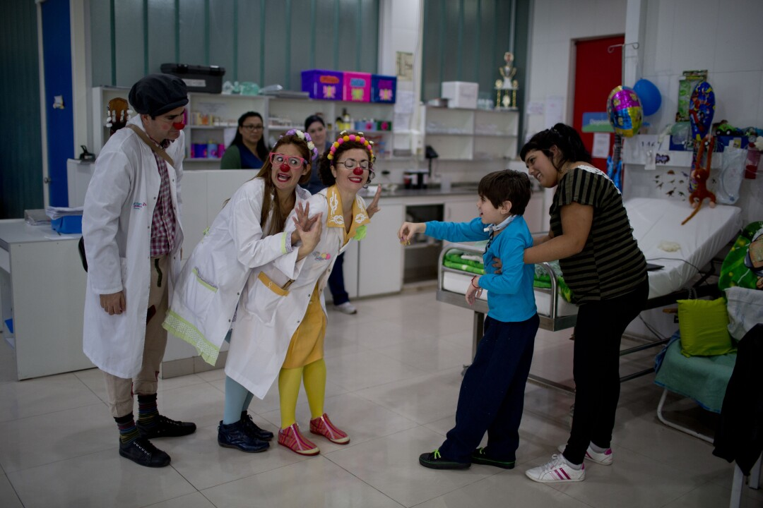 Clowns perform for Alejo Lacone at a pediatric hospital in Buenos Aires in 2015.