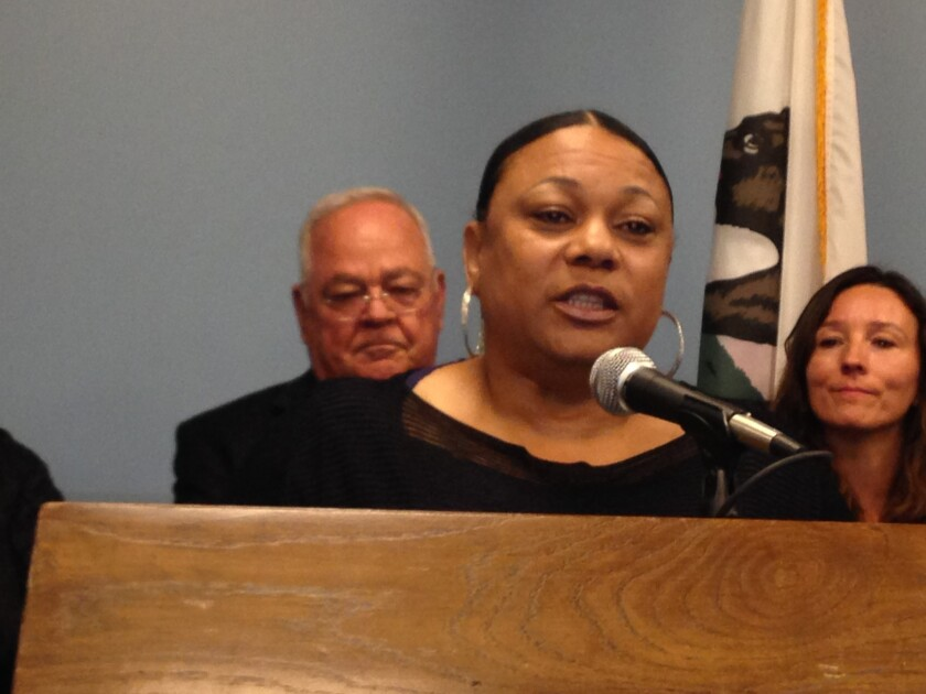 Bus Driver Sandra Lee, a union officer, speaks in support of a pact that will provide low-wage school workers $15 an hour in two years. Behind her are school board President Richard Vladovic and board member Monica Ratliff.