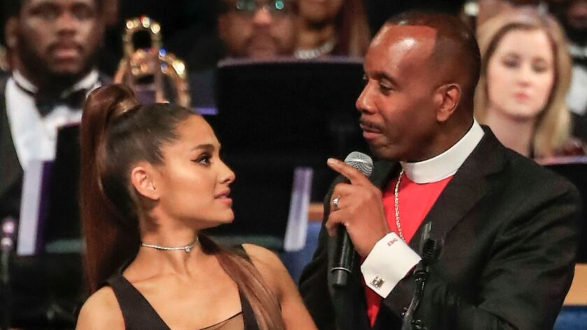 As Bishop Charles Ellis III wrapped his arm around pop star Ariana Grande during the funeral service for Aretha Franklin his fingers rose a little high.