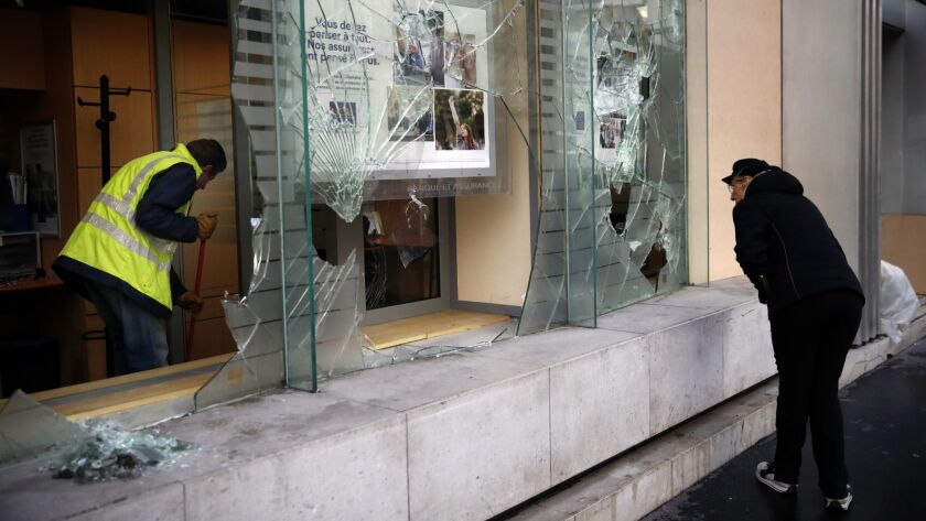 A worker clears debris in a bank as a man watches through smashed windows, in Paris, Sunday, Dec. 9,