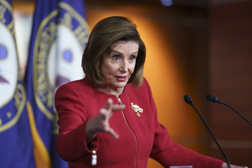 Speaker of the House Nancy Pelosi gestures while discussing President Biden's domestic agenda from behind a podium