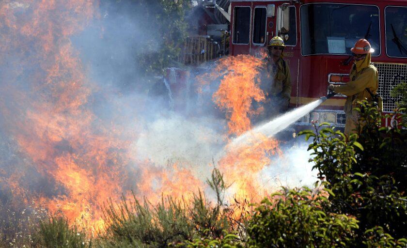 Bomberos tratan de extinguir el incendio declarado en el Point Mugu State Park, al norte de Los Ángeles en California.