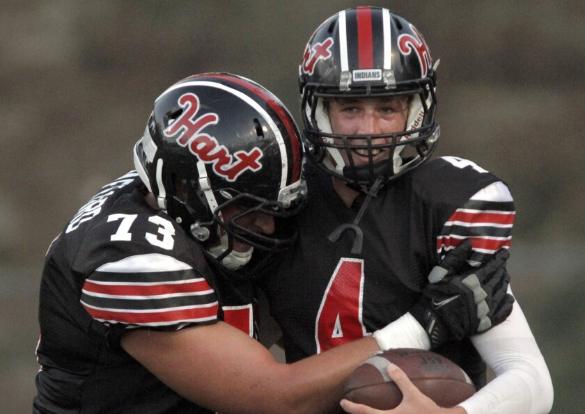 Erik Stafford, left, congratulates Trent Irwin after his touchdown during Hart's overtime victory against Chaminade.