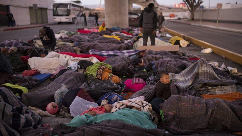 Migrants sleep under a bridge at the Chaparral border crossing in Tijuana, Mexico, Friday, Nov. 23,