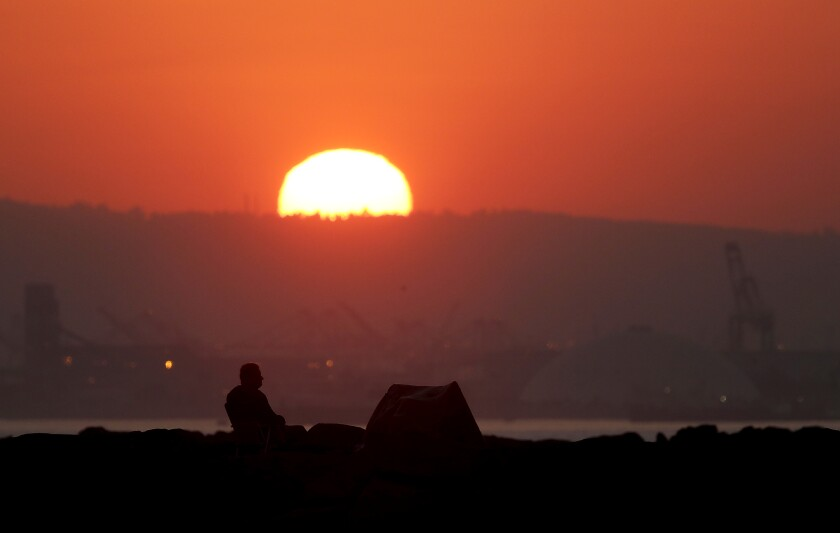 A man sits on the San Gabriel River jetty in Long Beach ahead of a heat wave that began Saturday.