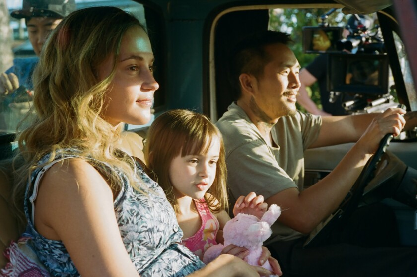 A woman, a little girl and a man sit in a truck.