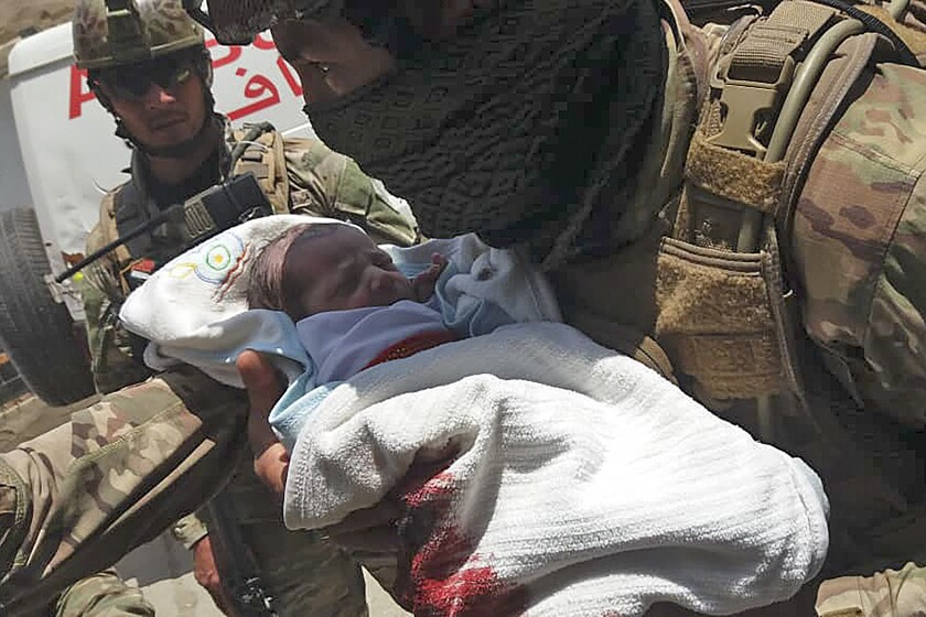 An Afghan security official carries a newborn baby from a hospital in the capital, Kabul,  after it was attacked May 12.