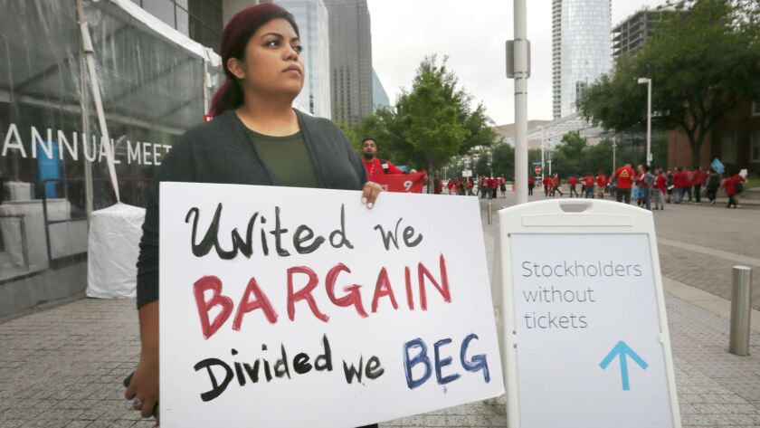 Union member Kristian Hernandez carries a sign during a Communication Workers of America protest outside AT&T's shareholders meeting in Dallas in April.