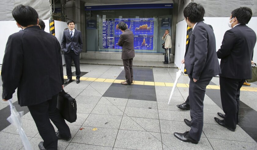 People look at an electronic stock board of a securities firm in Tokyo, Monday, Nov. 2, 2015. (AP Photo/Koji Sasahara)