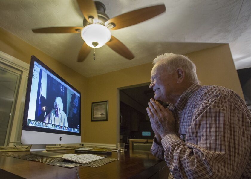 In this photo taken Nov. 6, 2015, Norwood Thomas talks with Joyce Morris via Skype. Below, a retirement community resident shares ideas for staying busy during quarantine.